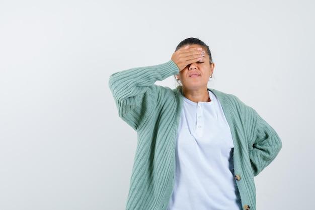 Tシャツ、手で目を覆い、疲れているように見えるジャケットの若い女性