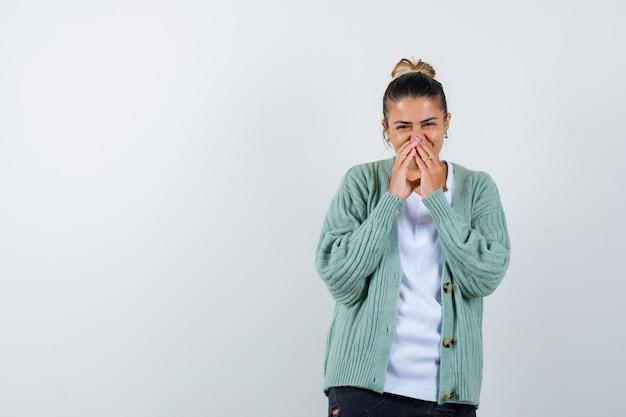 Tシャツ、手で口を覆い、かわいく見えるジャケットの若い女性