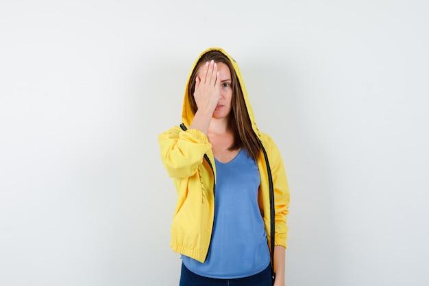 Tシャツを着た若い女性、目を握って賢明に見えるジャケット