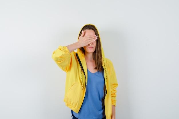 Молодая дама в футболке, куртке держит руку на глазах и выглядит спокойной