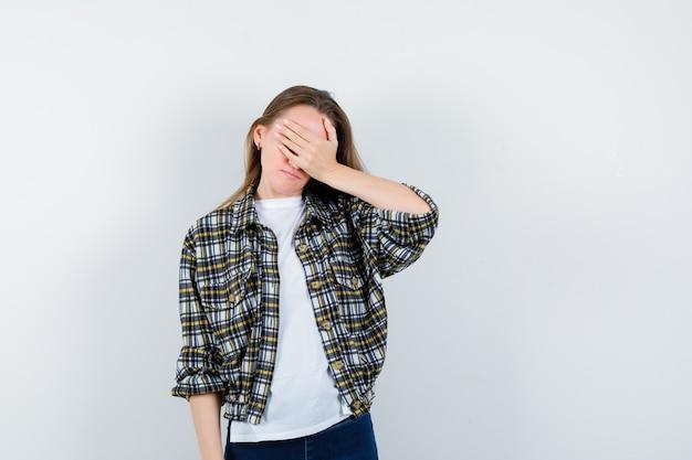 Молодая дама в футболке, куртке, джинсах, закрывающих глаза рукой и забывчиво выглядящих, вид спереди.