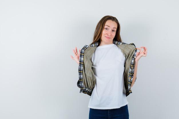 Tシャツ、ジャケット、ジーンズの若い女性がポーズをとってかわいく見える間、手でジャケットを保持している、正面図。