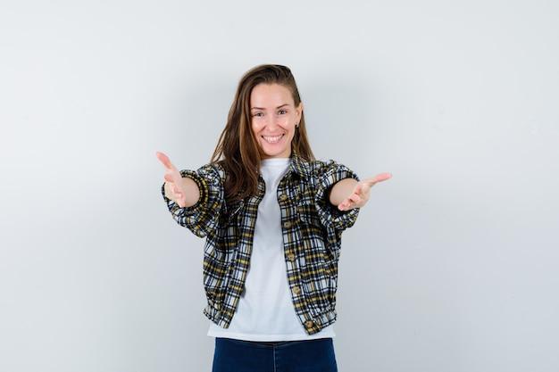 T- 셔츠, 재킷, 청바지 제스처를주고 즐거운, 전면보기를 보여주는 젊은 아가씨.