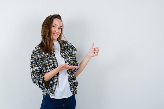 Tシャツ、ジャケット、ジーンズの若い女性が何かを歓迎し、魅力的に見える間、親指を立てて、正面図。