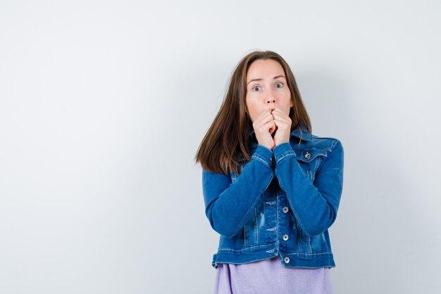 티셔츠를 입은 젊은 여성, 재킷은 입에 손을 대고 겁에 질린 표정으로 정면을 바라보고 있습니다.