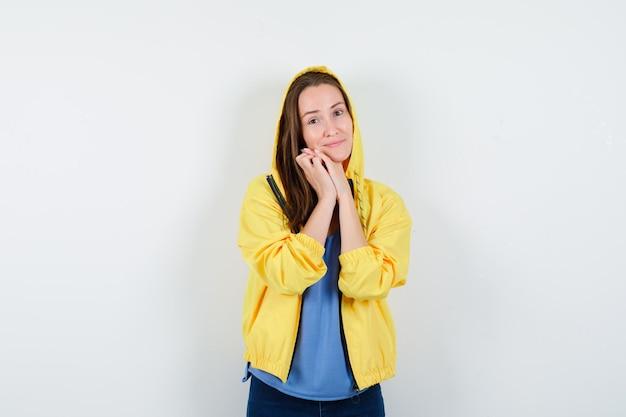 Tシャツを着た若い女性、握りしめられた手にあごをもたれ、きれいに見えるジャケット