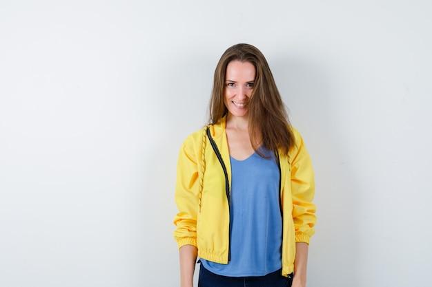 Молодая дама в футболке, куртке смотрит в камеру и выглядит заманчиво, вид спереди.