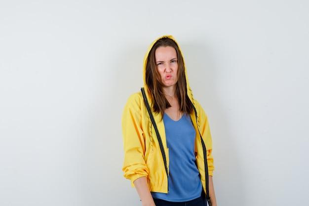 Tシャツを着た若い女性、ジャケットをかじりながらカメラを見て、暗い、正面図。