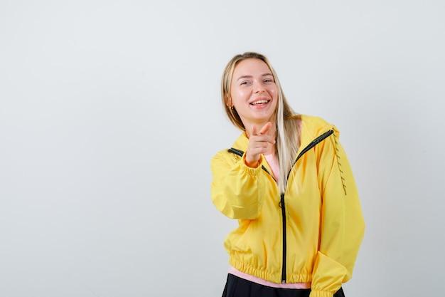 T- 셔츠, 재킷 포인팅 카메라와 낙관적 찾고 젊은 아가씨