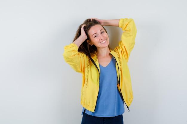 Tシャツを着た若い女性、頭に手をつないでポーズをとっているジャケット、めまい、正面図。