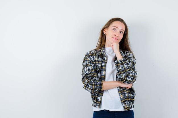 Молодая дама в футболке, куртке, подпирающей подбородок и выглядящей мечтательно, вид спереди.