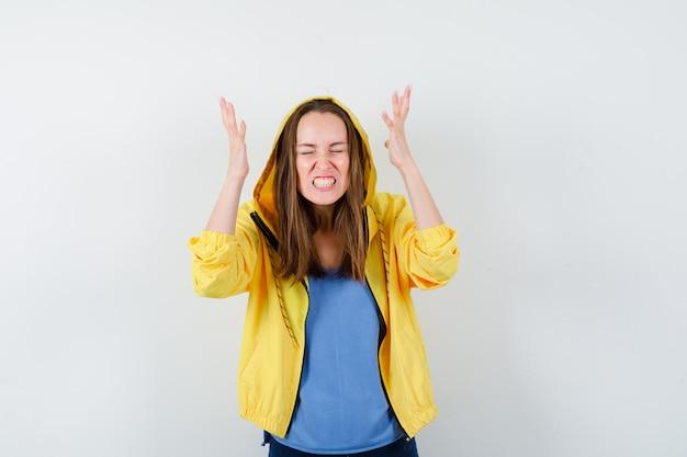 Tシャツ、ジャケットの挙手、歯を食いしばって、興奮しているように見える、正面図の若い女性。