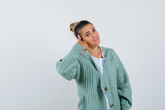 Tシャツを着た若い女性、ジャケットを見せて私をジェスチャーと呼び、自信を持って見える