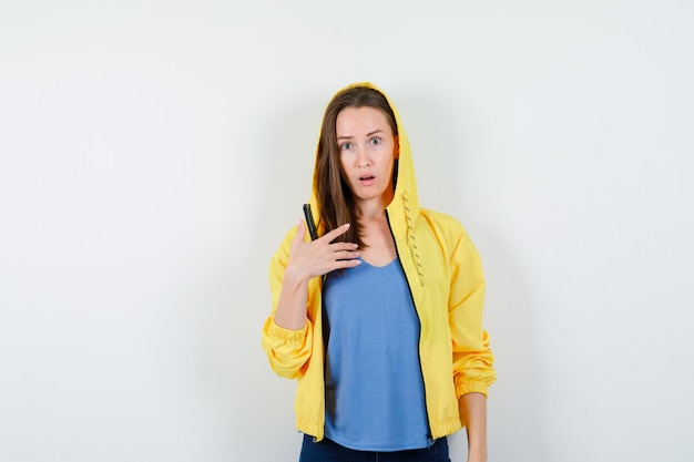 Tシャツを着た若い女性、疑わしい方法で自分自身を示し、困惑しているように見えるジャケット