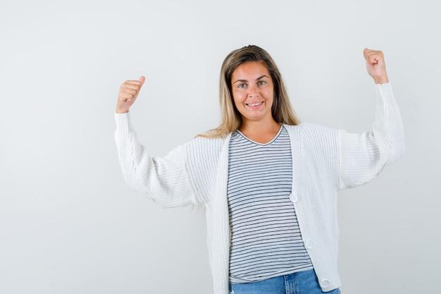 T- 셔츠에 젊은 아가씨, 팔의 근육을 보여주는 재킷과 자신감, 전면보기를 찾고.