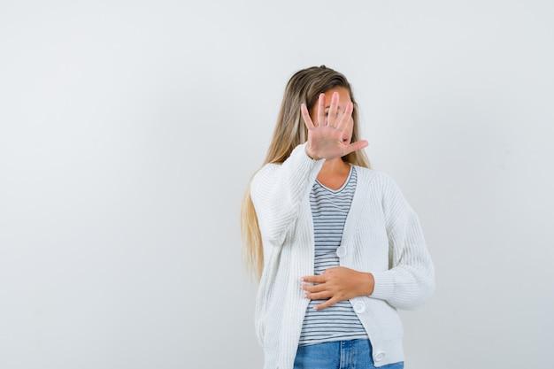 Молодая дама в футболке, куртка показывает жест остановки и выглядит раздраженным, вид спереди.