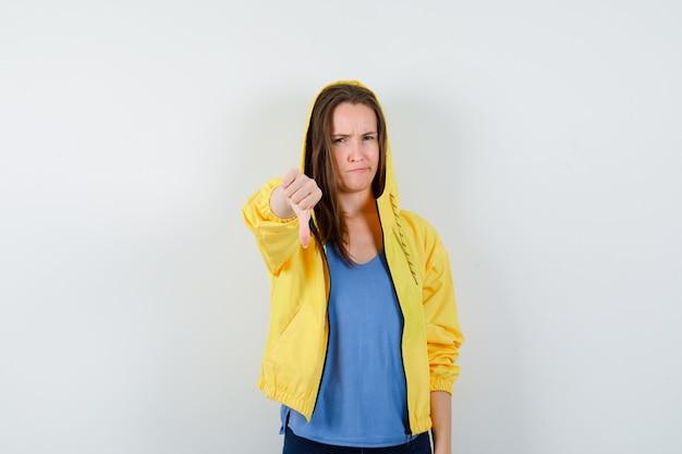 Tシャツを着た若い女性、親指を下に向けて不機嫌そうに見えるジャケット、正面図。