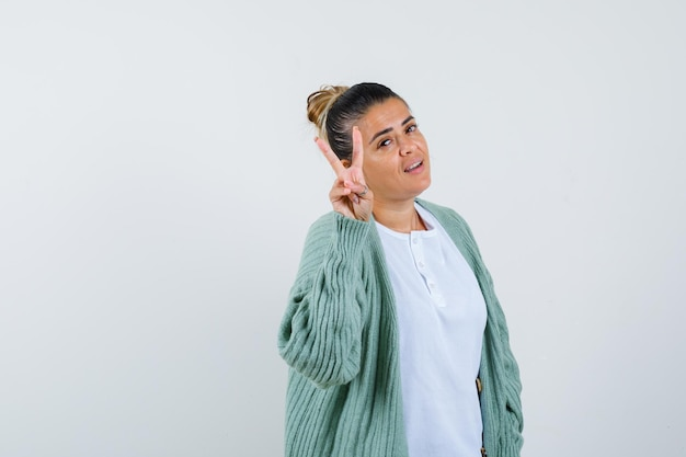 Tシャツ、勝利のサインを示し、幸運に見えるジャケットの若い女性