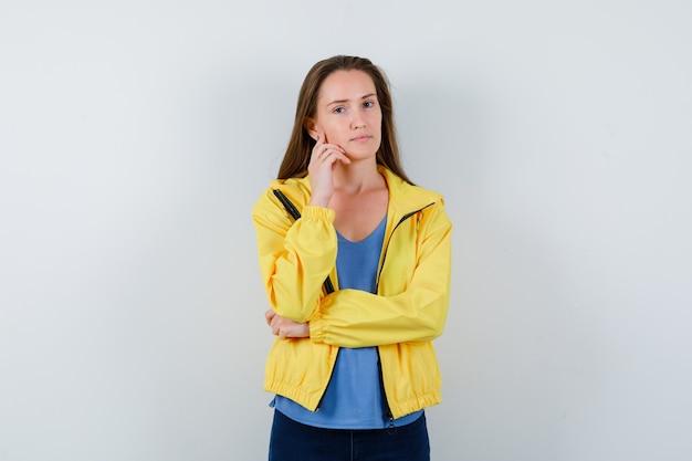 Tシャツを着た若い女性、思考ポーズで立っているジャケット、賢明に見える、正面図。