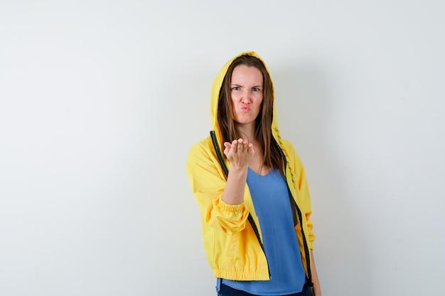 Tシャツを着た若い女性、ジェスチャーを質問し、怒っているように見える、正面図で手を伸ばしているジャケット。