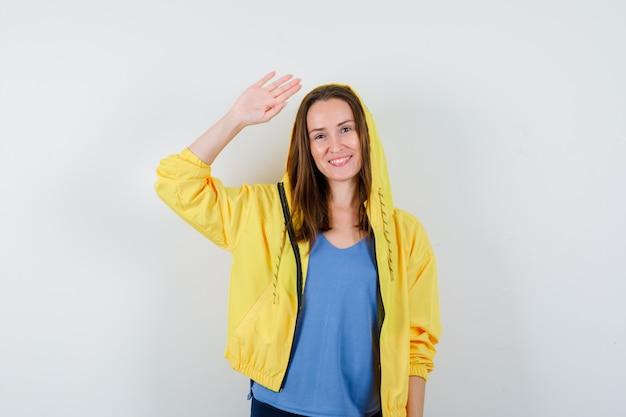 Tシャツを着た若い女性、挨拶と幸せそうに見えるために手を振るジャケット、正面図。