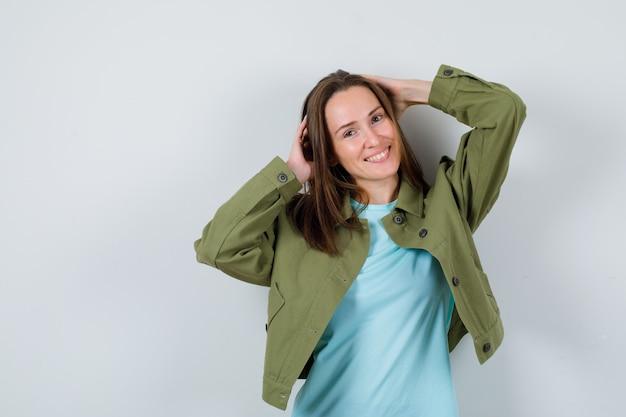Tシャツを着た若い女性、頭に手を当てて、うれしそうに見えるジャケット、正面図。
