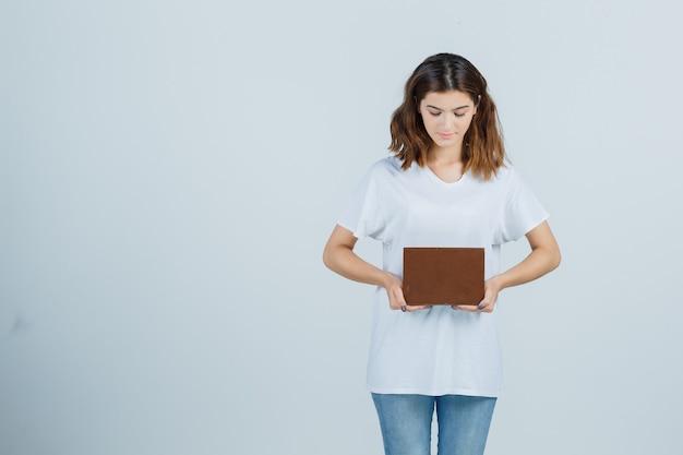 Tシャツを着た若い女性、思慮深く見ながら本を持っているジーンズ、正面図。
