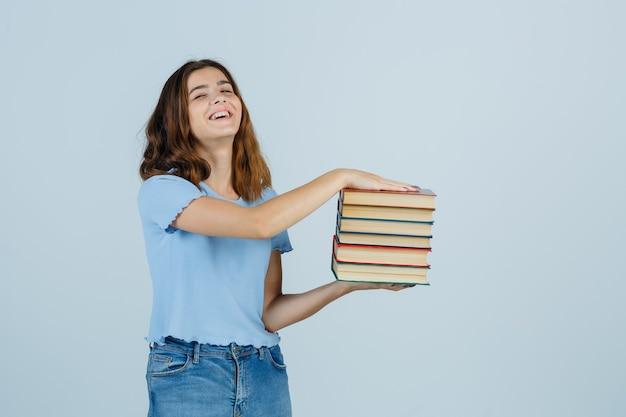 Tシャツを着た若い女性、本を持って桜を探しているジーンズ、正面図。