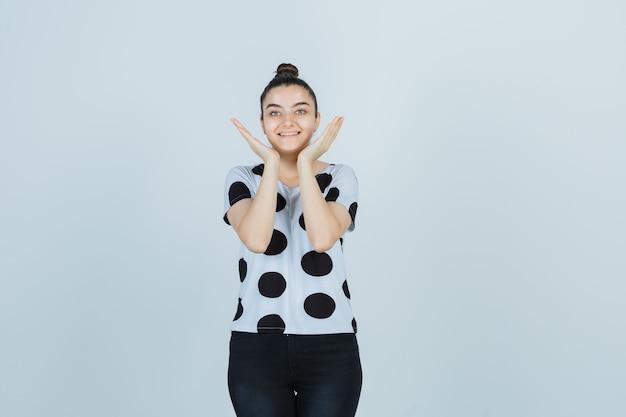 T- 셔츠, 뺨 근처 손을 잡고 귀여운, 전면보기 청바지에 젊은 아가씨.