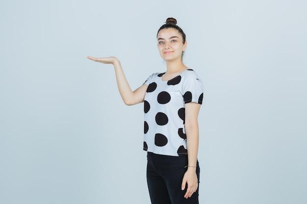 T- 셔츠에 젊은 아가씨, 청바지 뭔가를 잡고 자신감을 찾고, 전면보기.