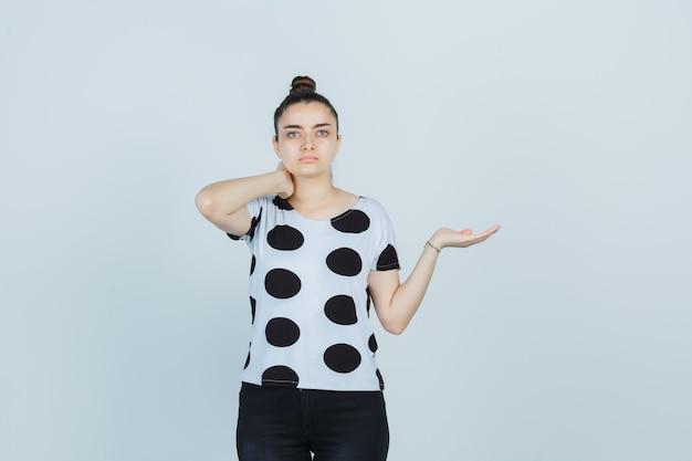 Tシャツを着た若い女性、首に手を握り、自信を持って見ながら何かを見せているふりをしているジーンズ、正面図。