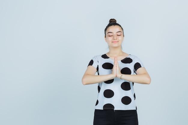 Tシャツを着た若い女性、ナマステのジェスチャーを示し、平和に見えるジーンズ、正面図。