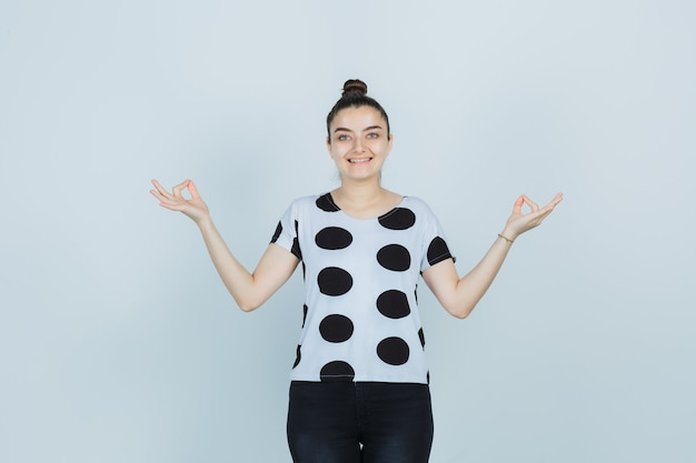 T- 셔츠, 확인 제스처를 표시 하 고 즐거운, 전면보기 청바지에 젊은 아가씨.