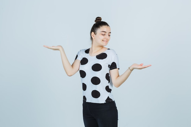Tシャツを着た若い女性、はかりのジェスチャーを示し、幸せそうに見えるジーンズ、正面図。