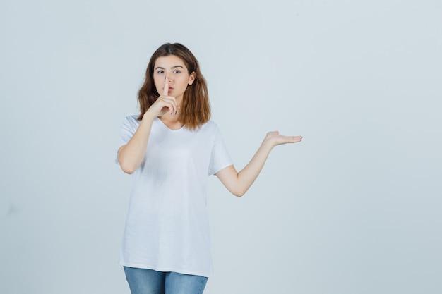 Девушка в футболке, джинсах показывает жест молчания, показывая что-то серьезное, вид спереди.