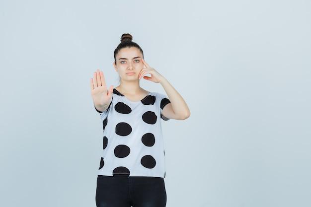 T- 셔츠, 청바지 중지 제스처를 표시 하 고 심각한, 전면보기에 젊은 아가씨.