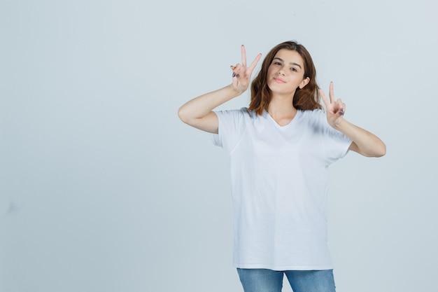 Tシャツを着た若い女性、勝利のサインを示し、陽気に見えるジーンズ、正面図。