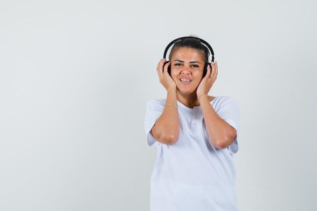 Девушка в футболке слушает музыку в наушниках