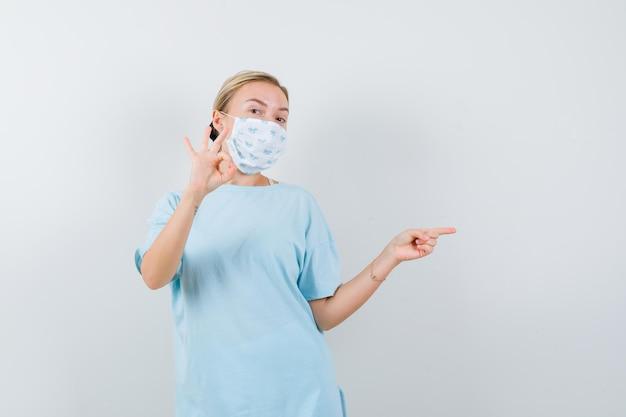T- 셔츠에있는 젊은 아가씨, 확인 표시를 표시하면서 오른쪽을 가리키는 마스크