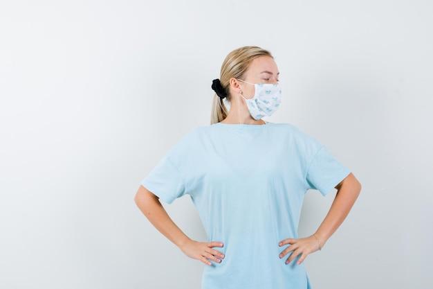 티셔츠에 젊은 아가씨, 허리에 손으로 포즈를 취하고 자신감을 보이는 마스크