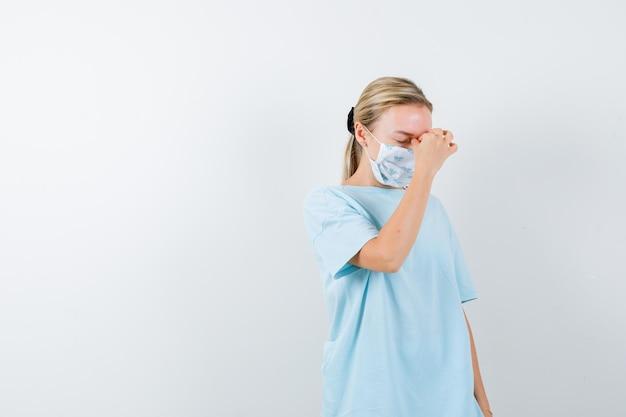 Молодая дама в футболке, в маске трет нос и глаза и выглядит усталой