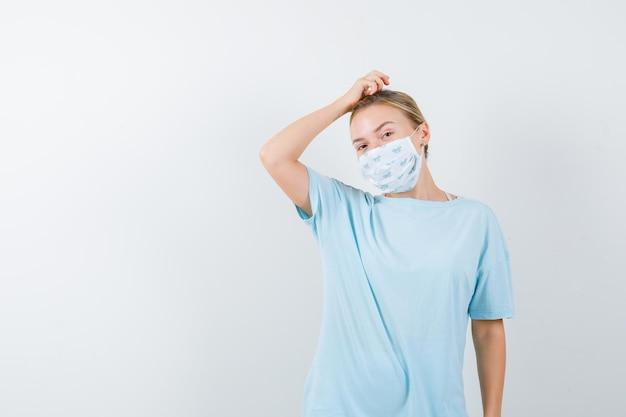 Tシャツを着た若い女性、頭を掻くマスク、思慮深い