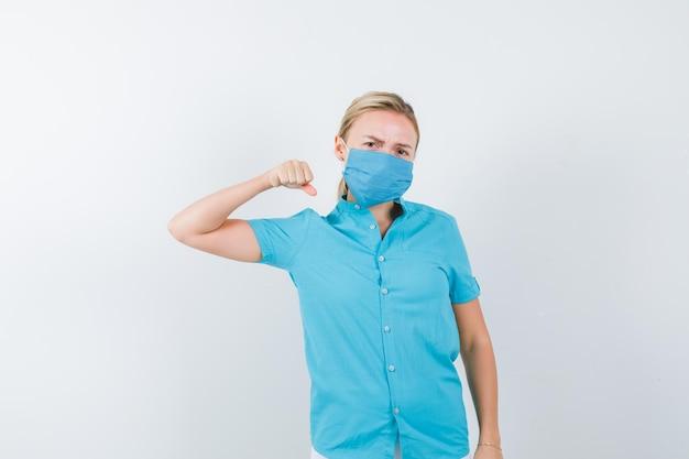Tシャツを着た若い女性、戦いのポーズで立って真剣に見えるマスク