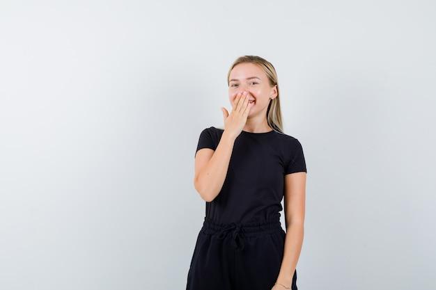 Молодая дама в футболке, штаны, взявшись за рот и выглядя счастливыми, вид спереди.
