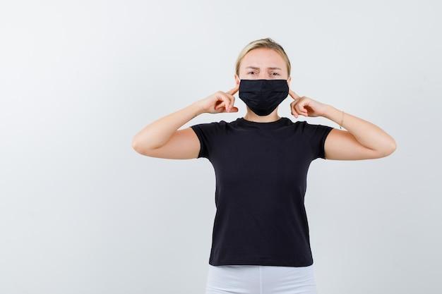Tシャツ、ズボン、医療用マスクの若い女性が指で耳を塞ぎ、イライラしているように見える
