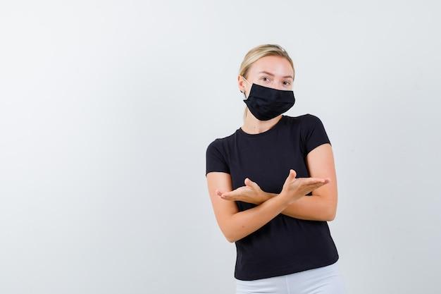 T- 셔츠, 바지, 손으로 교차 측면을 가리키는 의료 마스크 젊은 아가씨