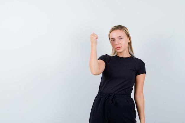 Tシャツを着た若い女性、勝者のジェスチャーを示し、自信を持って見えるパンツ、正面図。
