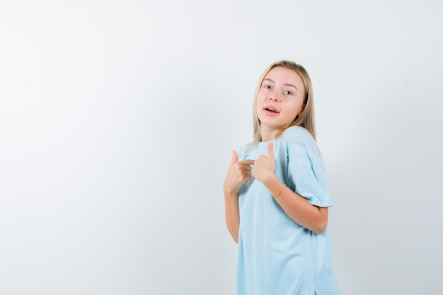 자신을 가리키고 자랑스럽고, 전면보기를 찾고 t- 셔츠에 젊은 아가씨.