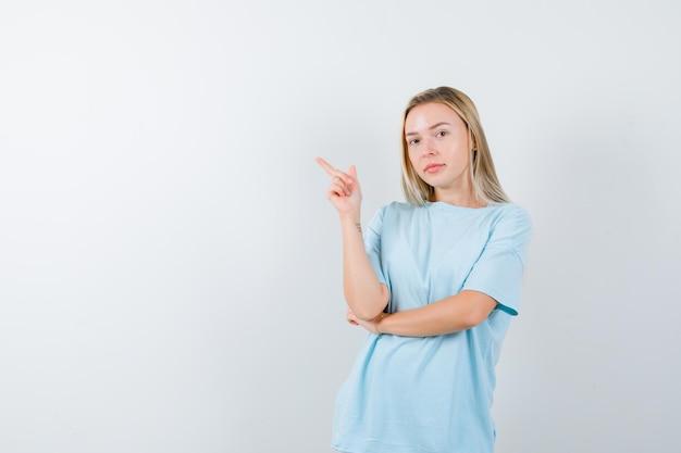 왼쪽 상단 모서리를 가리키고 고립 된 자신감을 찾고 티셔츠에 젊은 아가씨