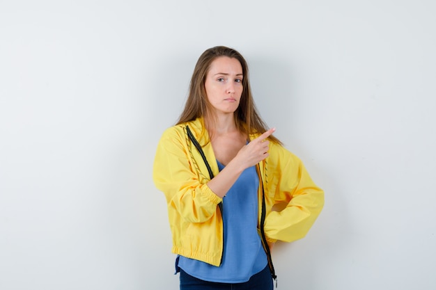 右上隅を指して、賢明な、正面図を探しているtシャツの若い女性。